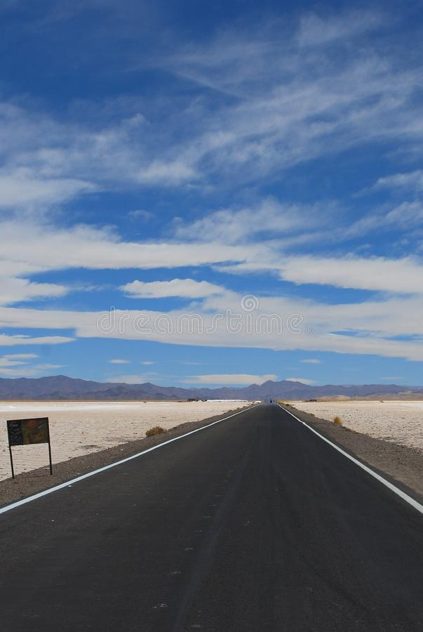 Endless Road. Over the Salinas Grandes salt flats in Argentina royalty free stock image