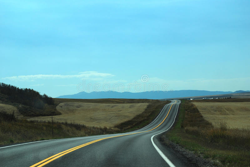 Endless road. Taken near Jackson hole, after harvesting,Hay stacked on pasture.endless road stock images