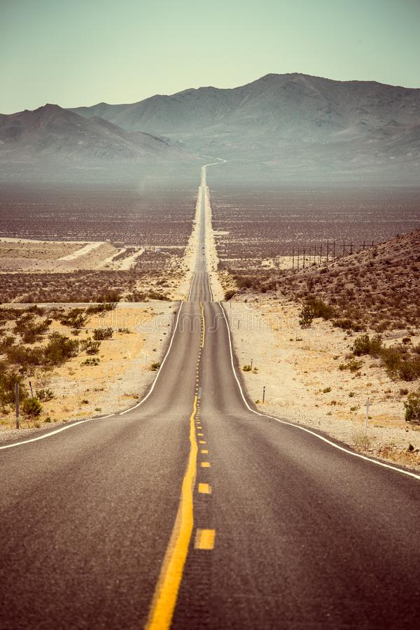 Endless straight road in the American Southwest, USA. Classic panorama view of an endless straight road running through the barren scenery of the American royalty free stock photo