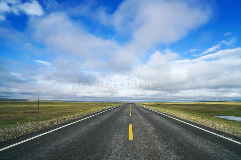 Endless straight road on plain with blue sky and white clouds. There is an endless straight road on plain to far away under blue sky and white clouds. Taken in royalty free stock photography
