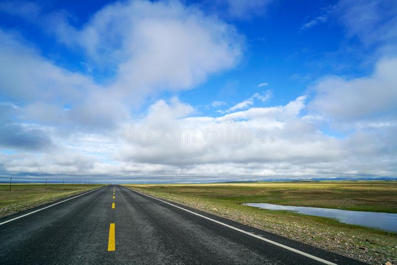 Endless straight road on plain with blue sky and white clouds. There is an endless straight road on plain to far away under blue sky and white clouds. Taken in stock images
