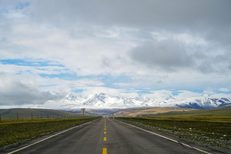 Endless straight road to snow mountains on plain with blue sky and white clouds. There is an endless straight road on plain to far away under blue sky and white royalty free stock image