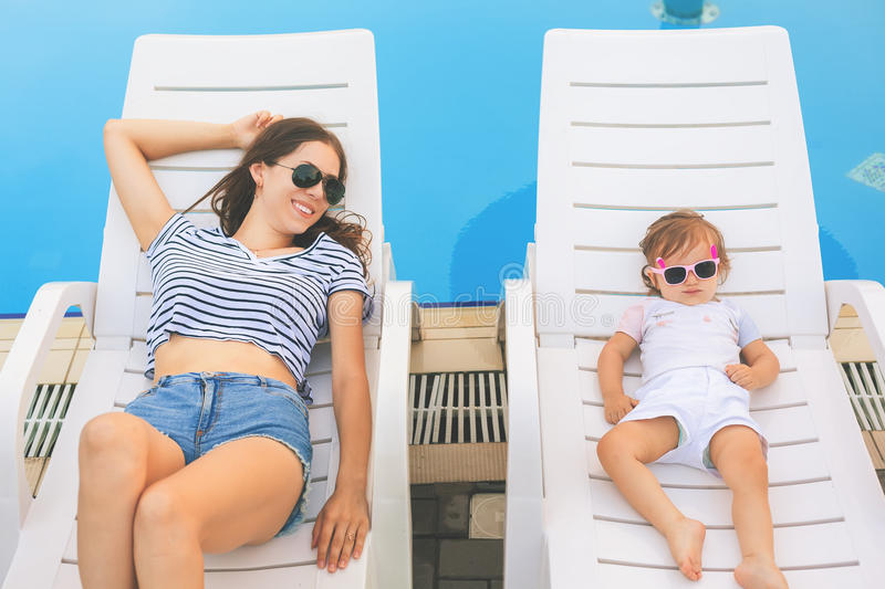 Endless summer. Cute baby and mother relaxing at sunbed royalty free stock photography
