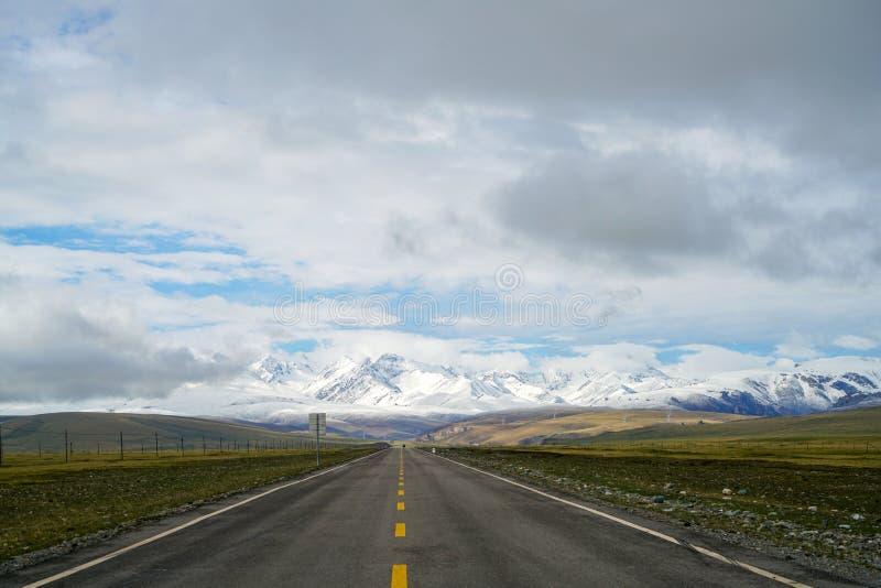 Endlose gerade Straße, zu schneien Berge auf Ebene mit blauem Himmel und weißen Wolken lizenzfreies stockbild