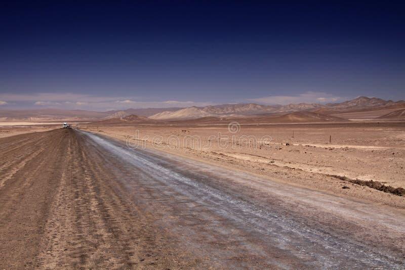 Endloser Schotterweg zur Unendlichkeit der flachen Hochebene des Salzes, die zum blauen wolkenlosen Himmel kontrastiert lizenzfreie stockbilder