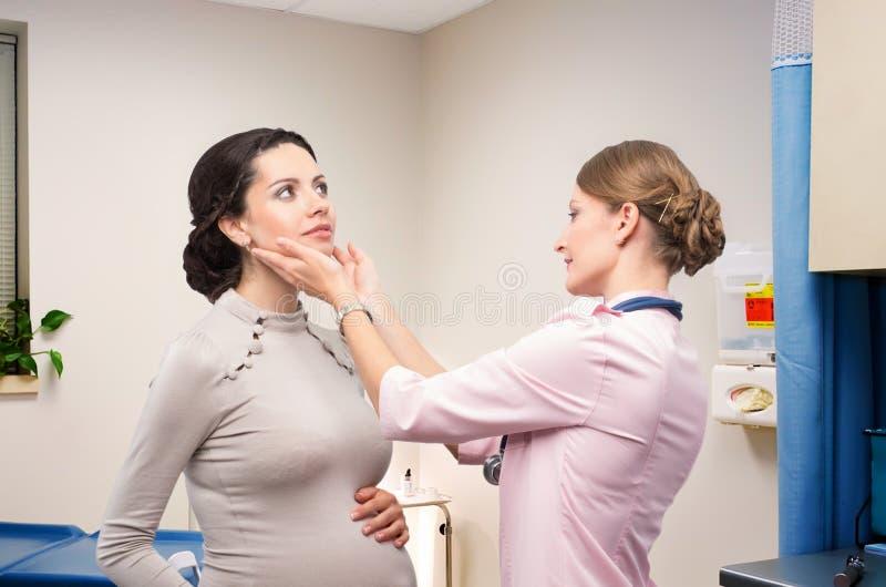 Endocrinologue de docteur vérifiant la thyroïde enceinte images libres de droits