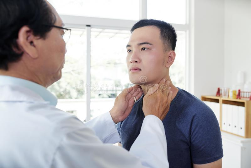 Endocrynologist checking thyroid of patient. Doctor palpating neck of young men when checking thyroid royalty free stock photography