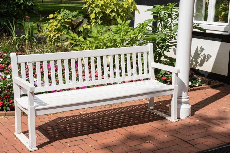 Endroit au repos - le blanc a laqué le banc en bois dans le jardin image stock