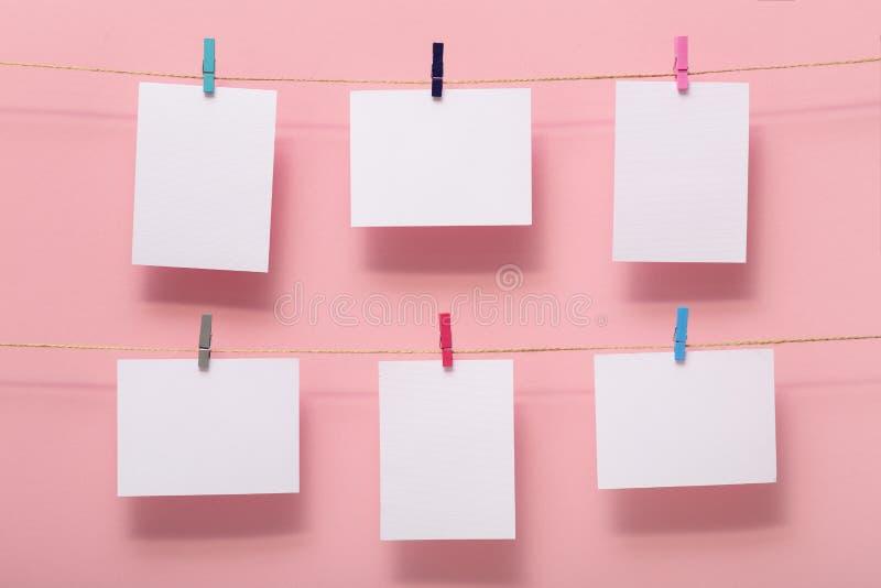 Endroit pour des cartes de photo des moments de la vie, blancs vides attachés à une corde de toile avec des agrafes de papeterie  photos libres de droits