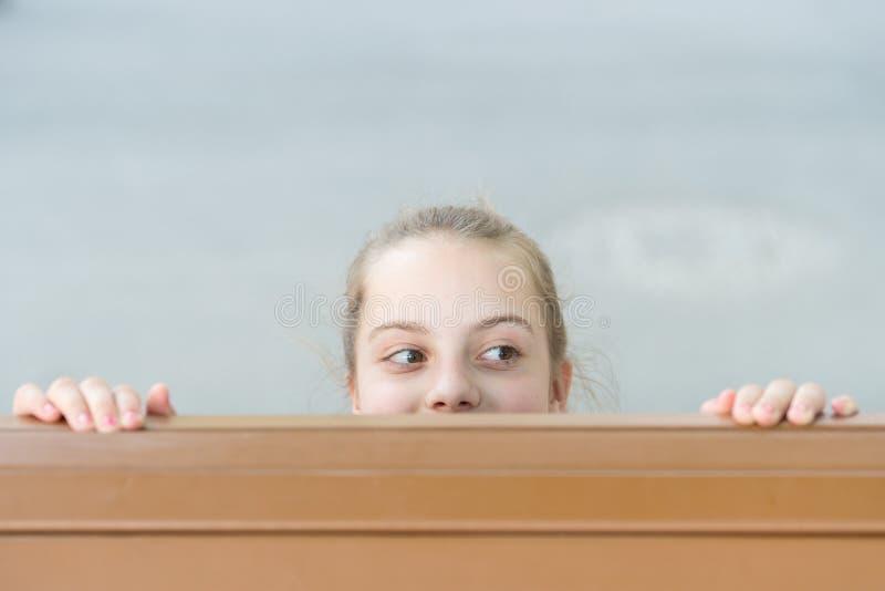 Endroit secret pour la dissimulation Petit enfant mignon se cachant sous la table Peu fille se cachant et piaulant avec la curios photographie stock