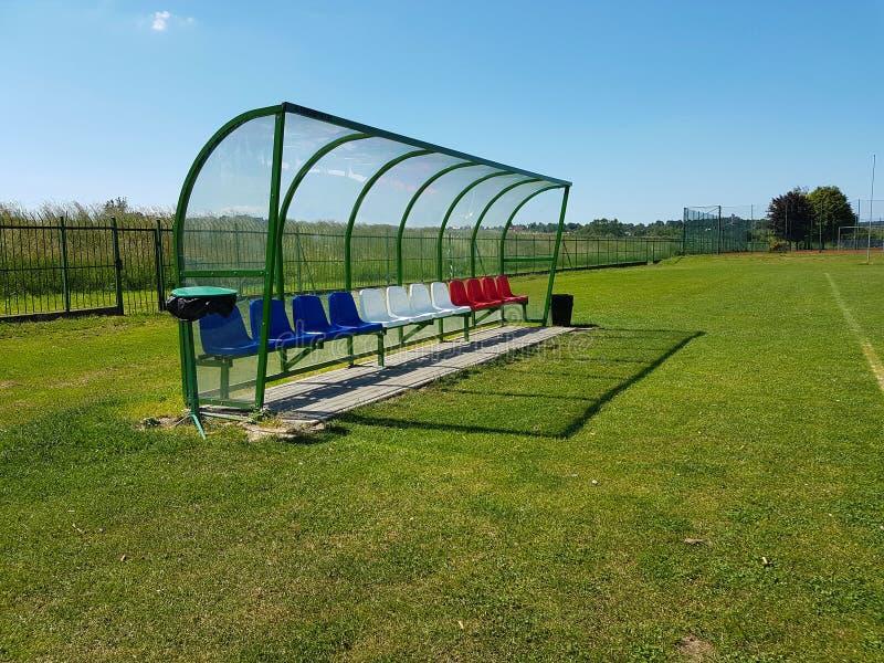 Endroits pour des entraîneurs et des joueurs de réservation sur le terrain de football Le plastique a coloré des bancs sous un au photo stock