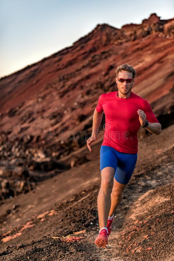 Endurance training fitness man on trail run running outside. Athlete runner in sportswear sunglasses, compression clothes, smart. Watch stock images