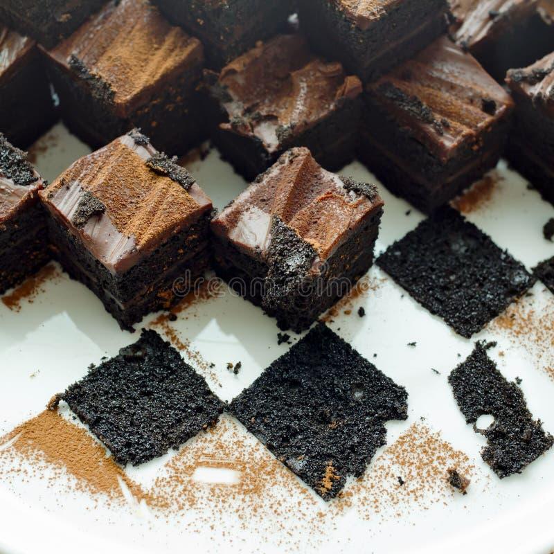 Endureça brownies do chocolate na placa branca com os leavings das brownies imagens de stock royalty free