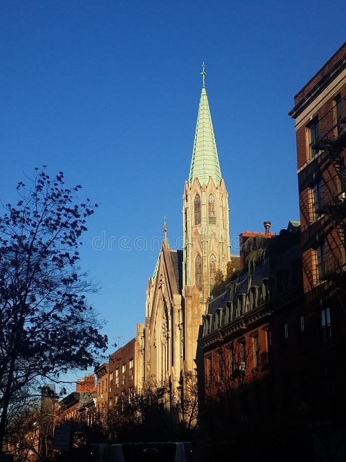 Enduring church with copper spire detail and stunning Gothic architecture in historic neighborhood street. Located in the historic Chelsea district of New York stock images