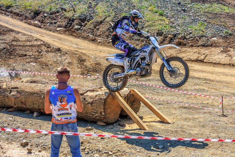 Enduro摩托车竟赛者克服在越野地形轨道的障碍在摩托车越野赛竞争在晴朗的夏日 免版税库存图片