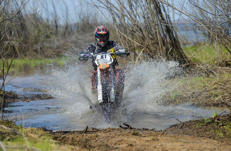 Enduro摩托车通过与大飞溅的泥乘坐 免版税库存图片