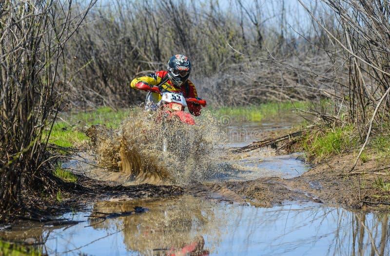 Enduro摩托车通过与大飞溅的泥乘坐 免版税库存照片
