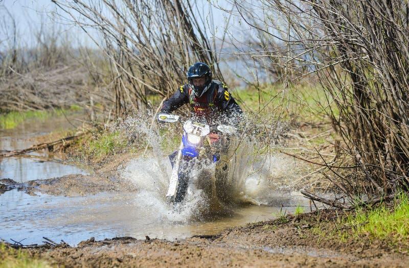 Enduro摩托车通过与大飞溅的泥乘坐 免版税图库摄影