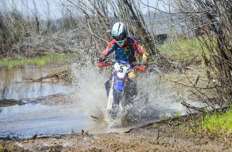 Enduro摩托车通过与大飞溅的泥乘坐 库存照片