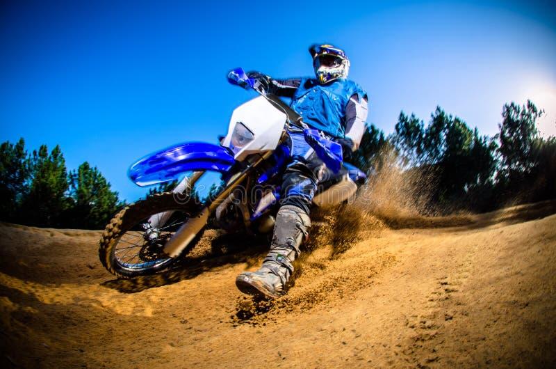 Enduro bike rider. On action. Turn on sand terrain stock image