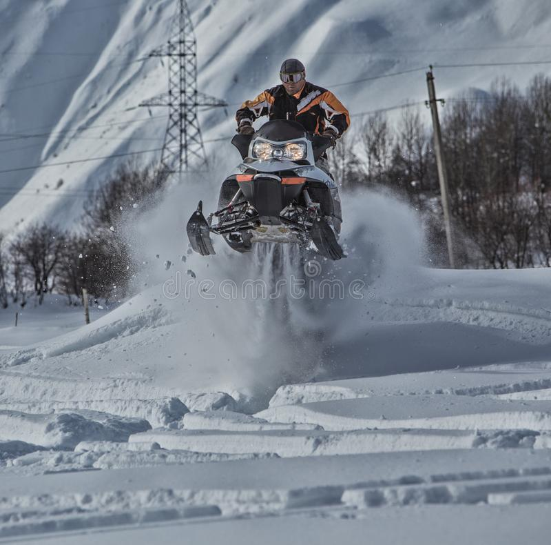 Enduro snowbike与土自行车的雪上电车旅途高在山 库存照片