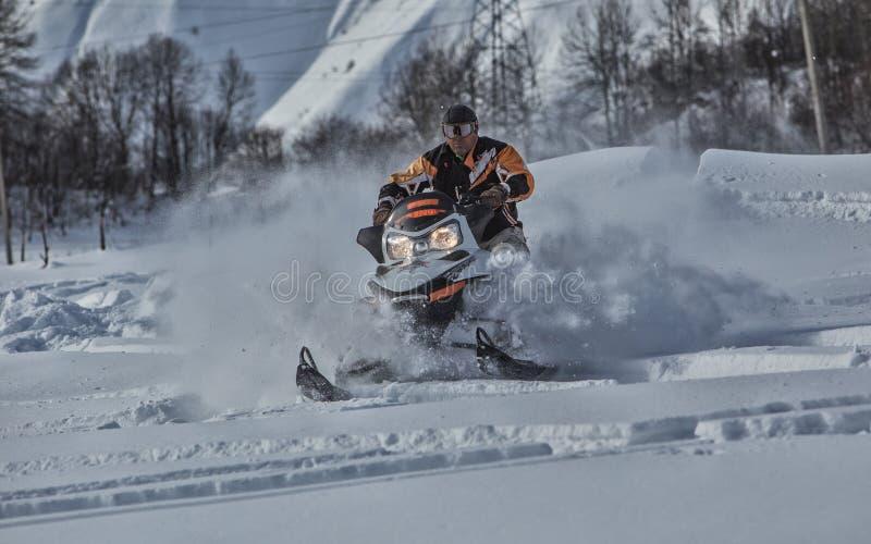 Enduro snowbike与土自行车的雪上电车旅途高在山 免版税库存图片