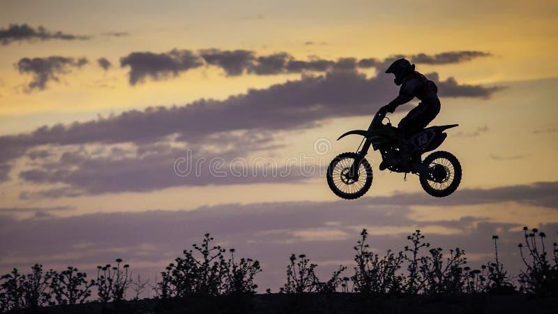 Endurofiets die bij zonsondergang springen royalty-vrije stock fotografie