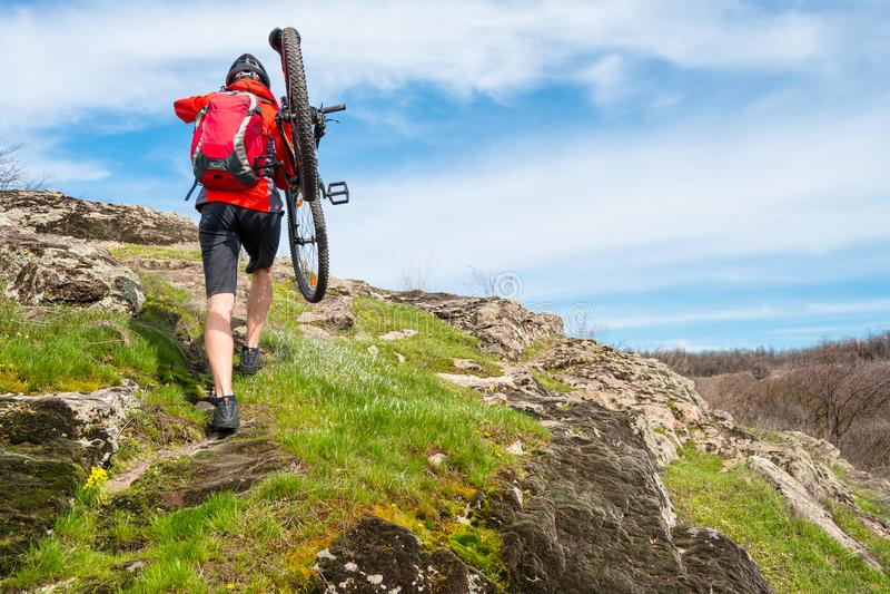 Endurofietser die zijn Bergfiets tot Mooi Rocky Trail nemen Extreem Sport en Avonturenconcept royalty-vrije stock afbeelding