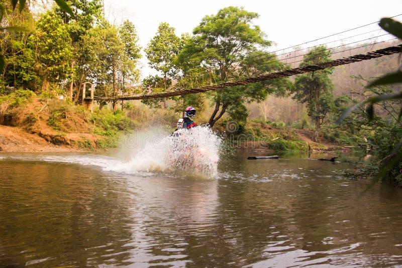 Enduromotorcykeltävlingsföraren för den suddiga bilden körde in i vattnet royaltyfria bilder