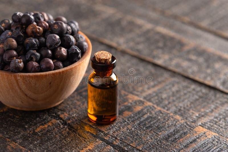 Enebro Berry Essential Oil en una tabla de madera apenada fotografía de archivo libre de regalías