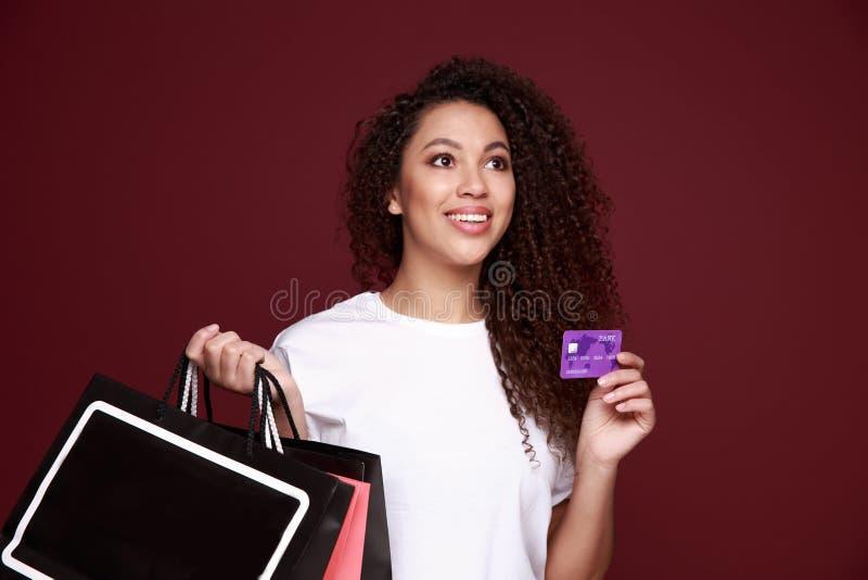 Enegreça sexta-feira A menina afro-americana nos monóculos está guardando sacos de compras e um cartão de crédito e está sorrindo fotografia de stock