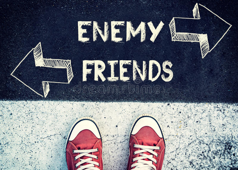 Enemy and friends. Student standing above the sign enemy and friends royalty free stock photo