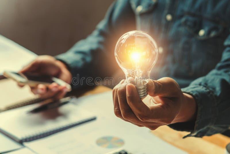 Energía de ahorro de la idea del concepto mano del hombre de negocios que sostiene la bombilla i fotos de archivo libres de regalías