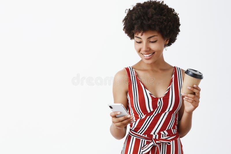 Energía de impulso con noticias frescas y café delicioso Mujer afroamericana moderna femenina encantadora en equipo elegante foto de archivo libre de regalías
