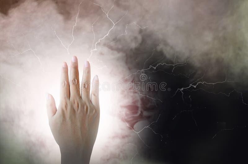 Energía eléctrica fuerte de una mano en fondo negro imágenes de archivo libres de regalías