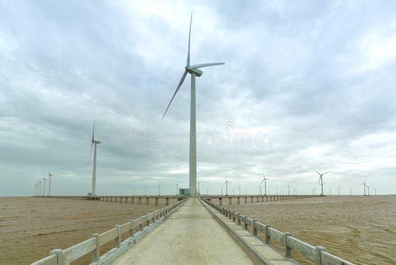 Energía limpia, central eléctrica de energía eólica con un camino a las turbinas de viento gigantes en el mar imágenes de archivo libres de regalías