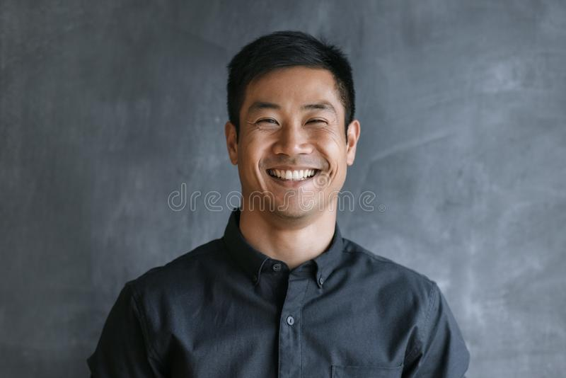 Energetic Asian businessman standing by a blank office chalkboard stock image