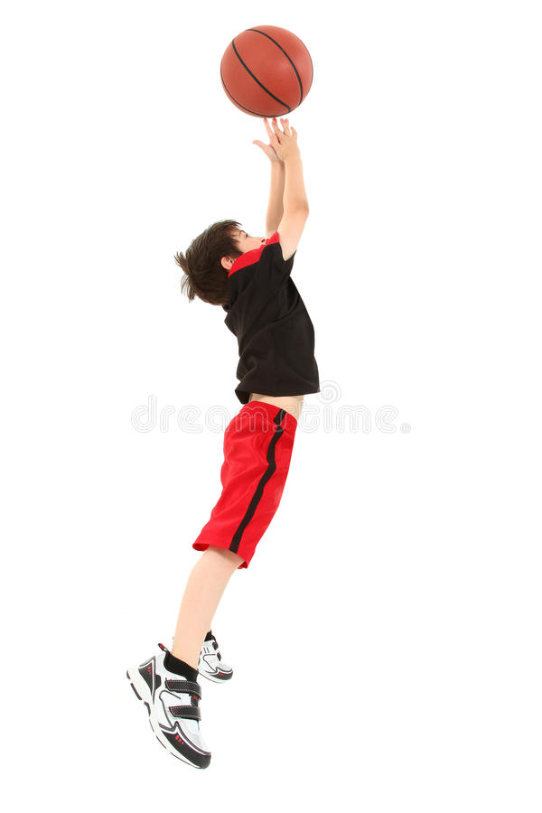 Energetic Boy Child Jumping with Basketball. Energetic 8 year old boy child in basketball uniform jumping for shot royalty free stock photo