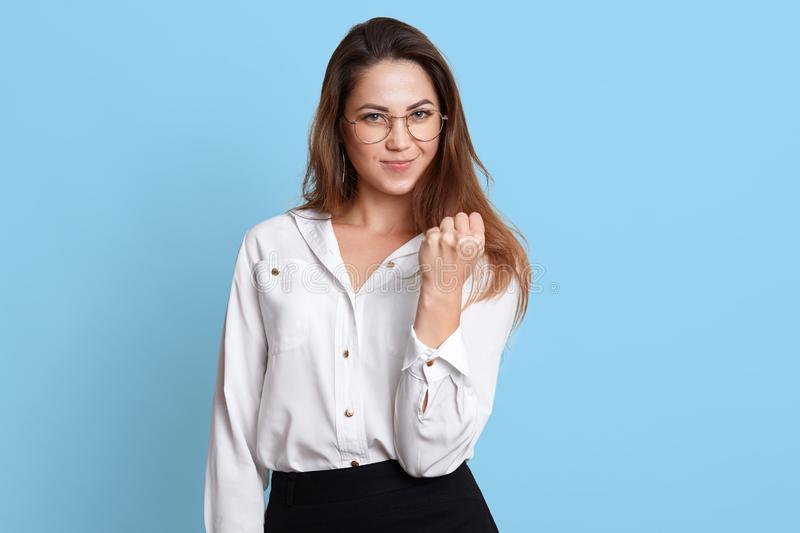 Energetic confident executive shows clenched fist over light blue background. Long haired threatening female wears unbutton white stock images