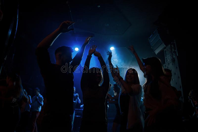 Energetic crowd. Group of people that enjoying dancing in the nightclub with beautiful lightings royalty free stock images