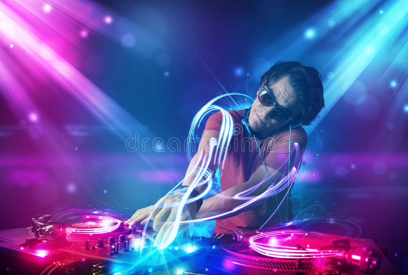 Energetic Dj mixing music with powerful light effects royalty free stock images