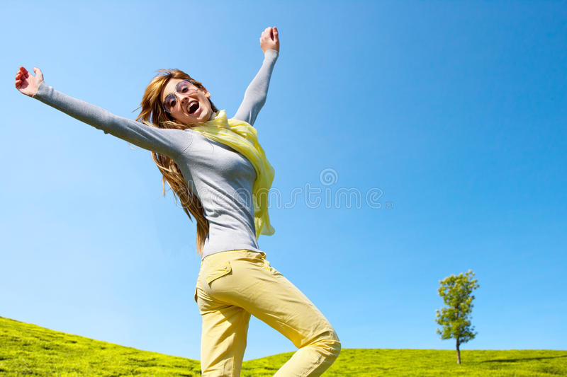 Energetic girl with open arms outdoors.