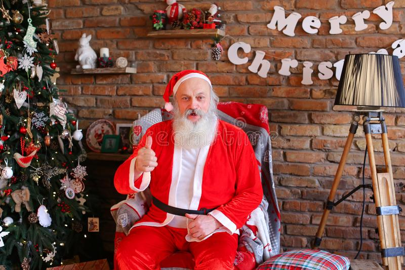 Energetic Santa Claus raises thumb up, sitting on armchair in fe. Christmas grandfather shows that everything good and fills everyone with positive mood in cozy stock photo