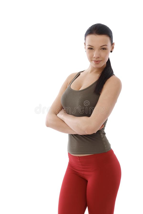 Energetic woman standing arms crossed. Young energetic woman in sportswear standing arms crossed royalty free stock photo