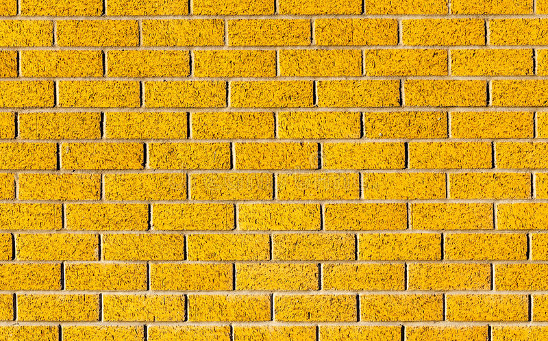 Energetic yellow brick wall as a background image with black vignette. stock images