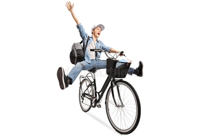 Energetic young male with a backpack riding a bicycle and gesturing happiness royalty free stock images