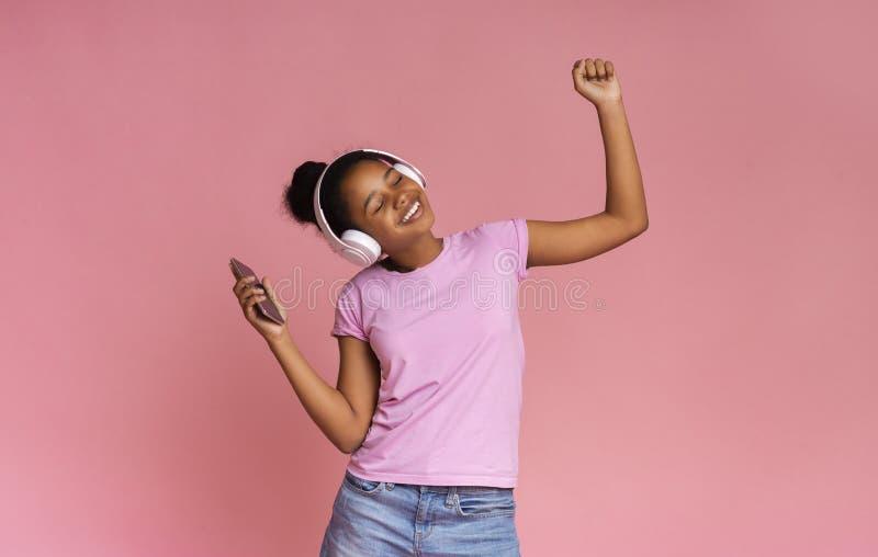 Energetisk tondansande, lyssna på favoritmusik med trådlösa hörlurar arkivbild