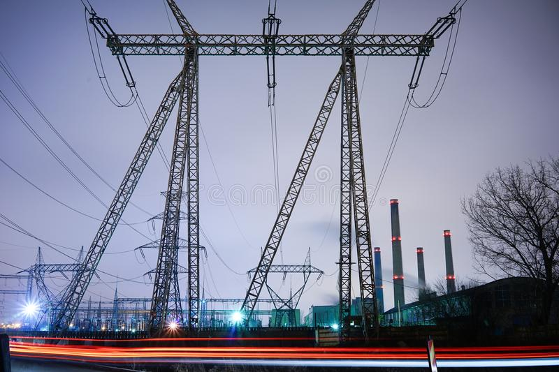 Energetycal flows. Grey image, red horizontal lines. Front view of structure of electric poles; Power plant, urban periphery High tension poles, transformation royalty free stock image