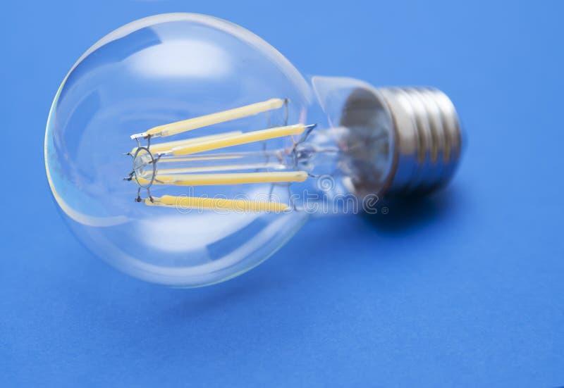 Energi - besparinglampa på en blå bakgrund arkivfoton