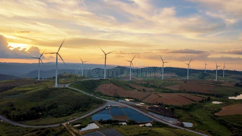 Energi för gräsplan för rengöring för lantgård för turbiner för solnedgånglandskapvind för utvalt arkivfoto